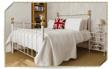wide shot of white iron and brass bed