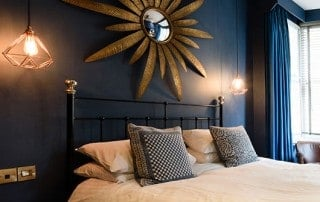 room shot of black iron and brass bed